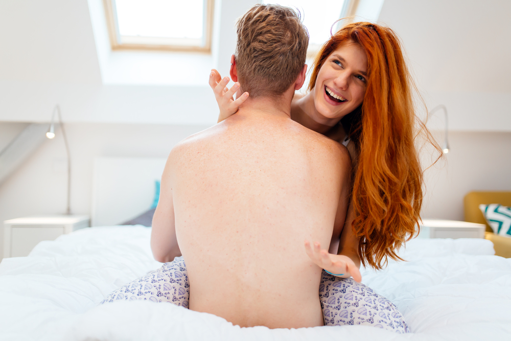 couple getting intimate in bed woman is happy that man is taking