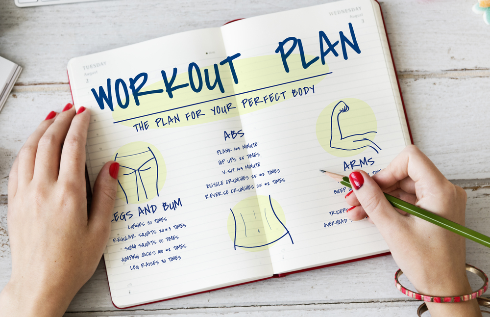 woman writing down workout plan in fitness journal
