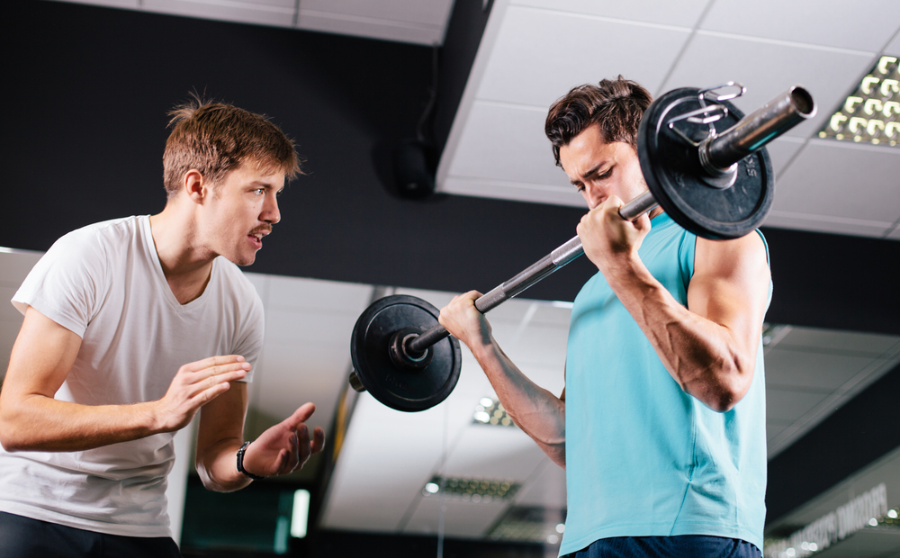 personal trainer motivating client lifting weights and talked about